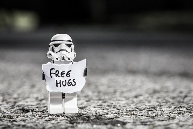 """Eine Stormtrooper-Figur hält ein Schild mit """"Free Hugs"""". Urheber: clement127 (https://www.flickr.com/photos/clement127/13661779374/)"""