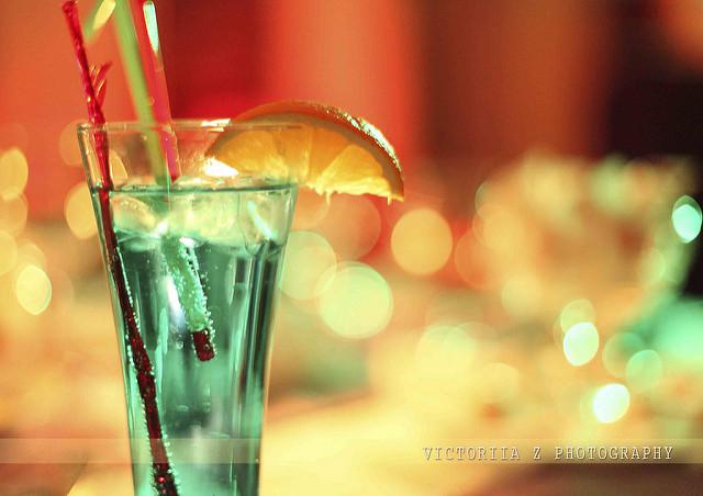 Grüner Drink mit Orange am Rand und mehreren Trinkhalmen