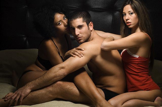 Zwei Frauen und ein Mann sitzen in Unterwäsche auf einem Bett.
