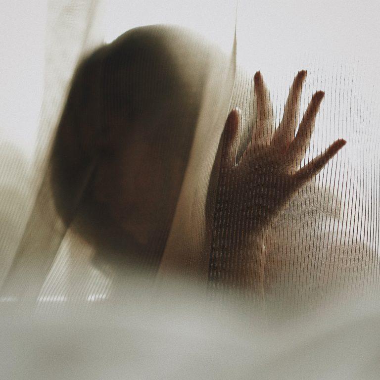 Frau hinter einem Vorhang (von Claudia Soraya/Unsplash)