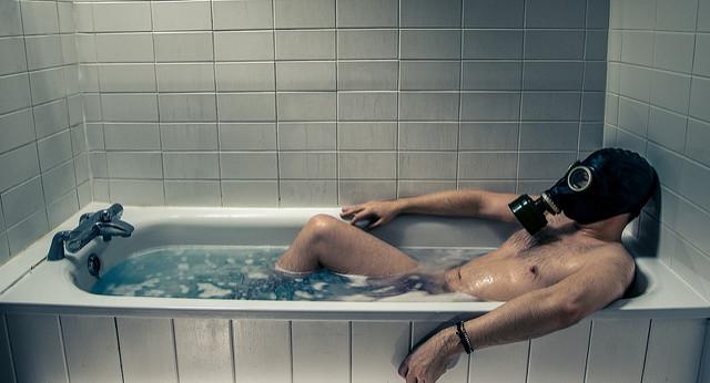Mann mit Maske liegt in der Badewanne