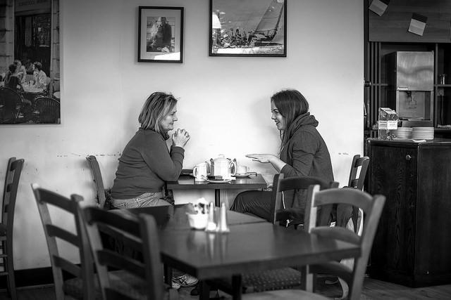 Zwei Frauen sitzen in einem Café und unterhalten sich.