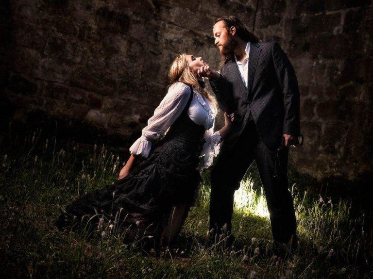 Paar steht vor einer Mauer, der Mann hält die Frau am Kinn und sieht ihr bedrohlich in die Augen