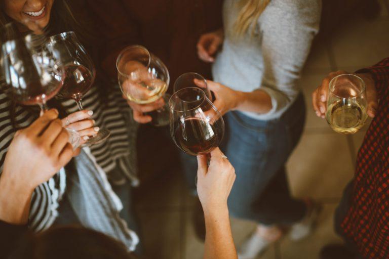 Mehrere Menschen stoßen mit ihren Weingläsern an.