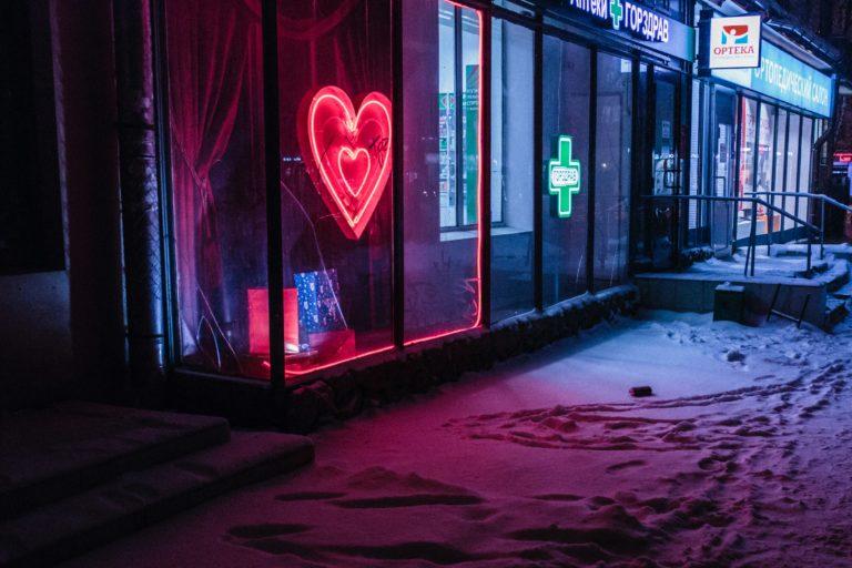 Schaufenster mit einem erleuchteten Herzen drinnen (Photo by Alexander Popov on Unsplash)