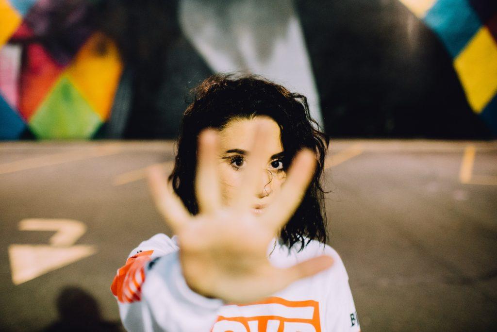 Eine Frau streckt ihre Hand abwehrend nach vorne aus.