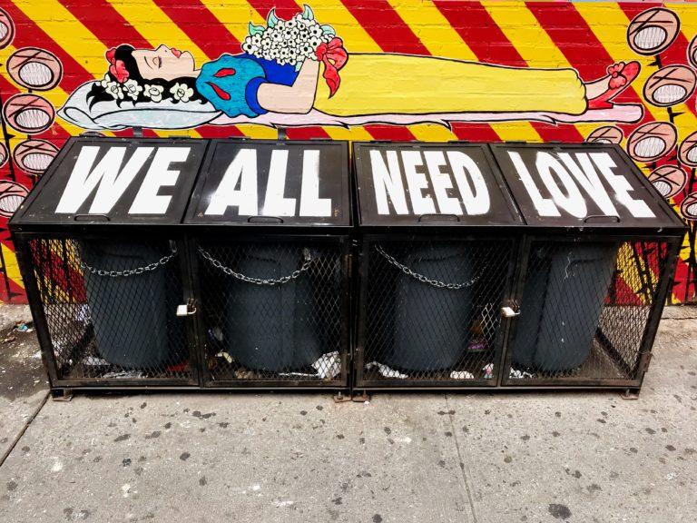 """Mülleimer mit der Aufschrift """"We alle need love"""", darüber ein Schneewittchen-Bild (Photo by Javier Ramos on Unsplash)"""