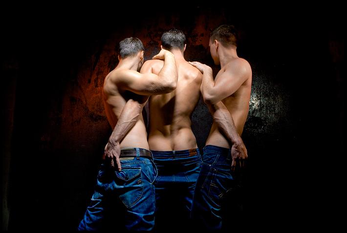 Drei Männer mit nacktem Oberkörper von hinten, die sich umarmen