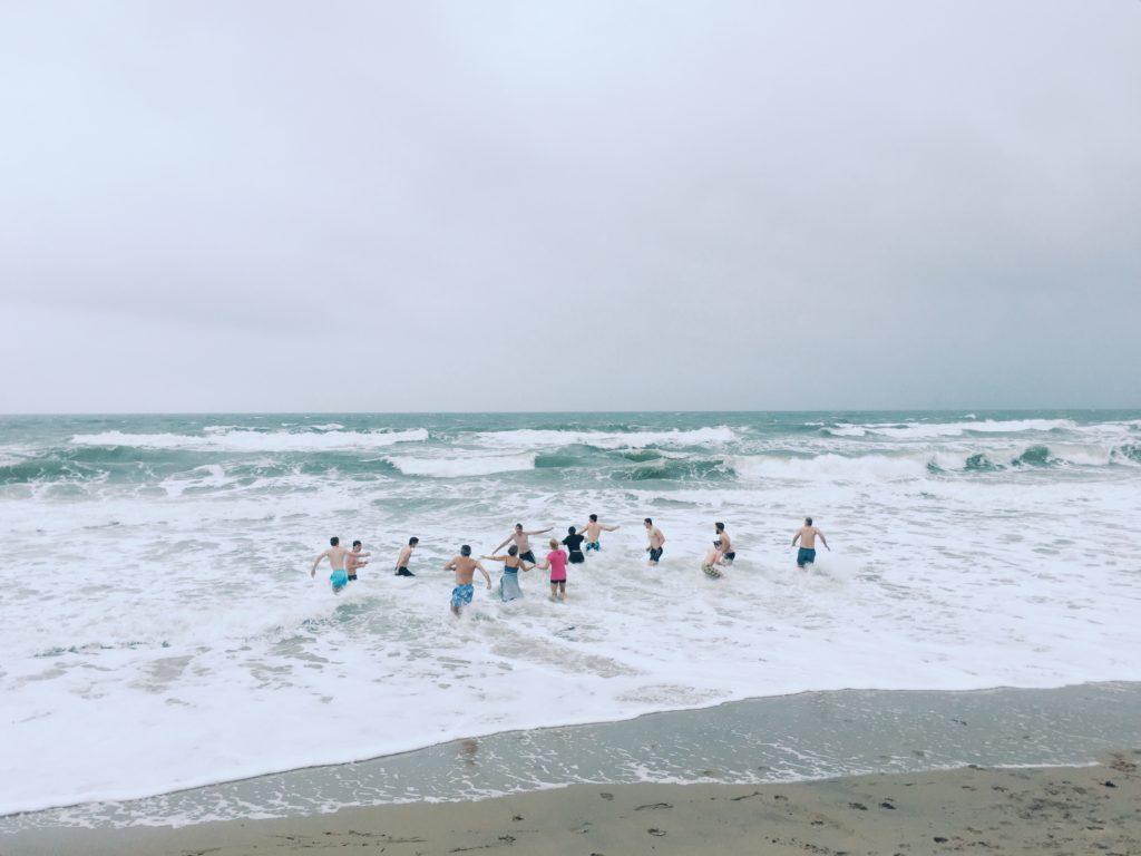 Eine Gruppe Menschen läuft ins Meer hinein (Quelle: Photo by Robert Bye on Unsplash)