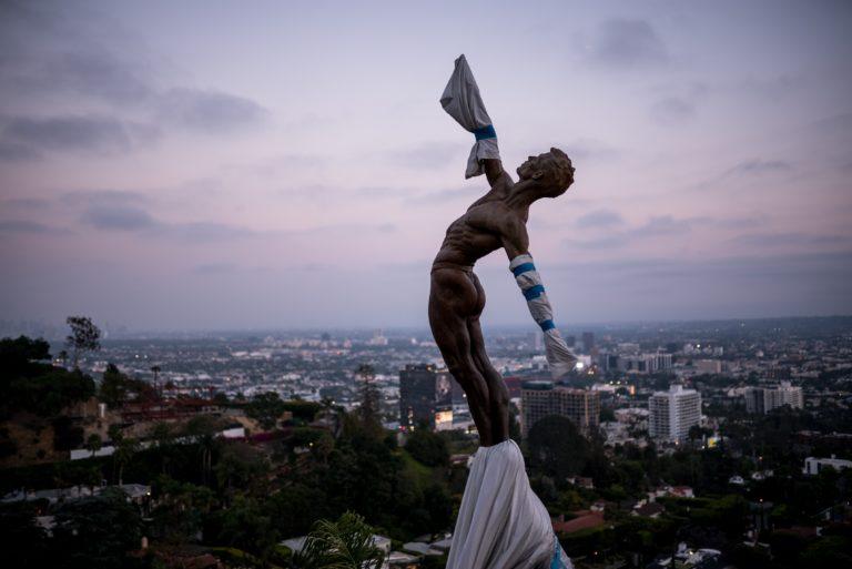Menschliche Statue reckt sich in den Himmel (Photo by Allison Heine on Unsplash)