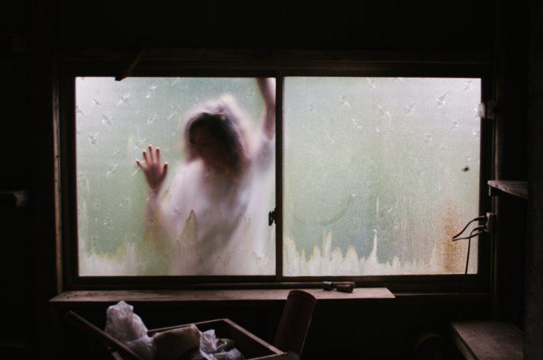 Frau steht vor dem Fenster und kommt nicht rein (Photo by Priscilla Du Preez on Unsplash)