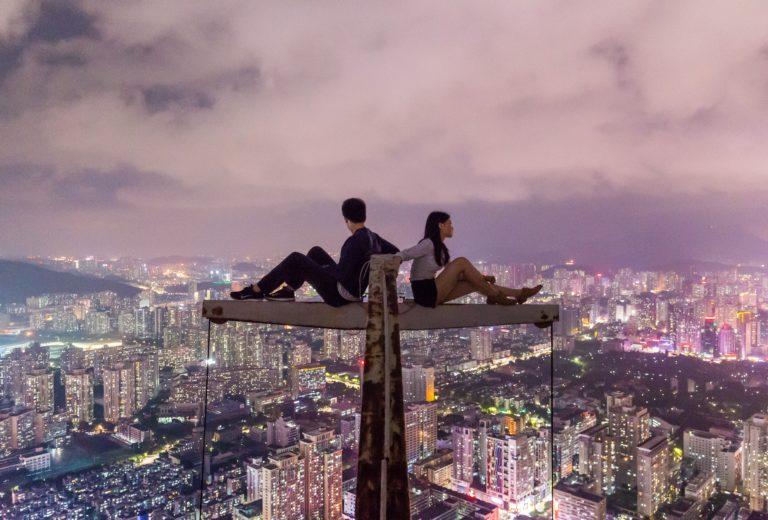 Frau und Mann sitzen auf einem dünnen Balken (Photo by Denys Nevozhai on Unsplash)